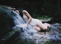 Young woman lying on small waterfall
